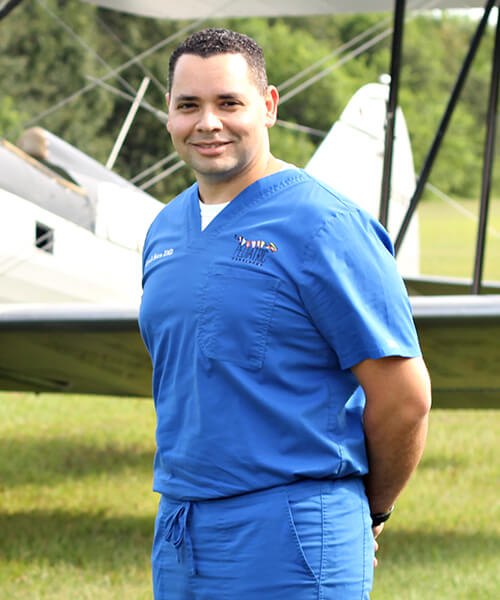 Dr. Luis A. Matos, one of our dentists in Stuart, FL, outdoors with an airplane in the background