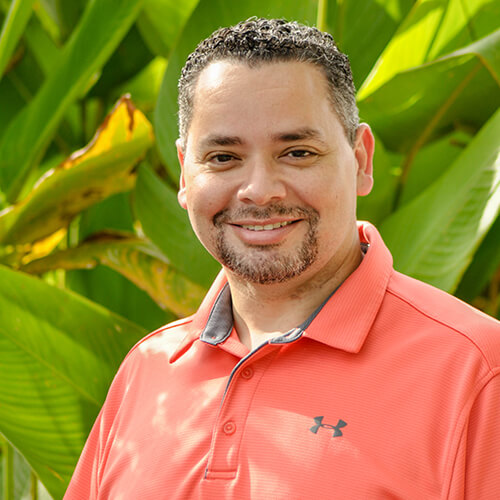 Dr. Luis A. Matos, a pediatric dentist in Stuart, FL, smiling in front of a tropical background