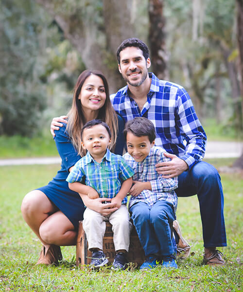 Dr. Shekha N. Patel, one of our caring dentists in Stuart, FL, outdoors with her husband and two young boys