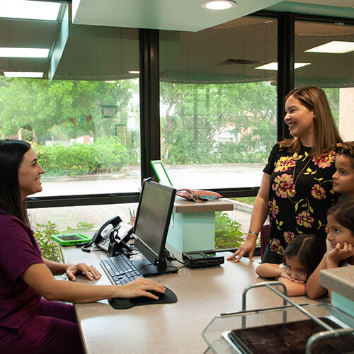 Front-desk staff talking to a parent with three kids during a visit to their pediatric dentists in Stuart, FL