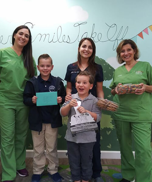 Our dental assistants smiling with two young patients at our office in Stuart, FL