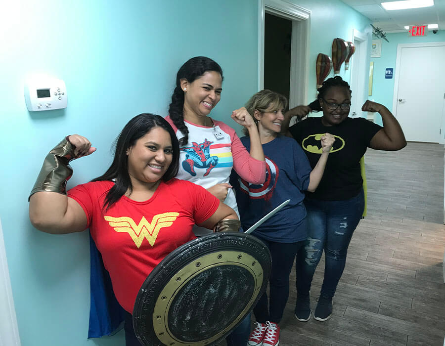 Some of our dental assistants wearing superhero costumes in the office