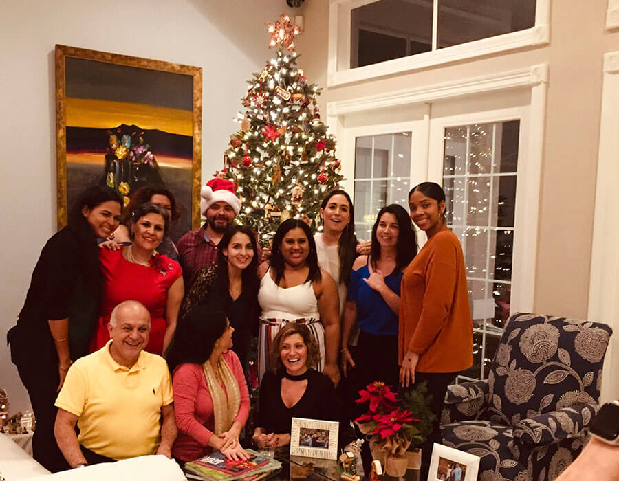 The Stuart dental team and their families in front of a Christmas Tree