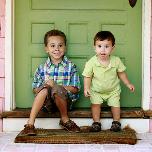 Two young patients of Stuart Pediatric Dentistry sitting on a doorstep and being given a VIP treatment