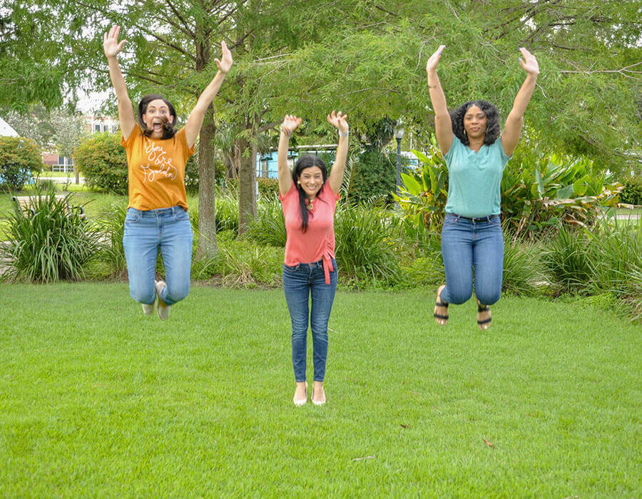 Some of our dental assistants jumping with their arms extended