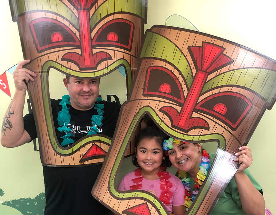 A young girl and her parents playing with Hawaiian themed props at the office